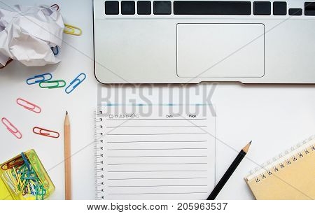 Top view of white office desk with laptop and other accessories; notebook pencil and paperclips