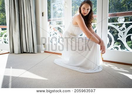 Beautiful bride looking away while crouching by door at home
