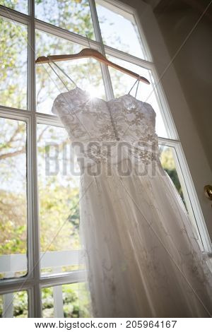 Low angle view of wedding dress hanging on window in dressing room