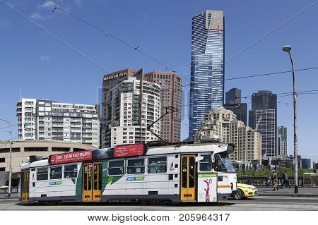 Melbourne, Australia: October 07, 2015: A tram is travelling along the road in Melbourne towards Flinders Street Station. Pedestrians are walking on the pavement and the Eureka Sky Tower is in the cityscape behind.