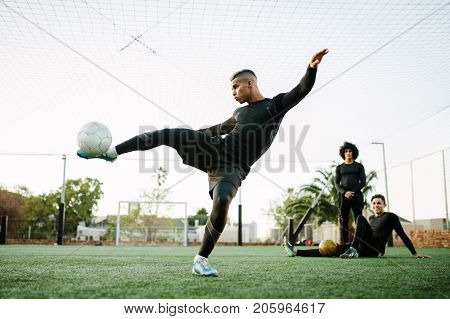 Soccer player kicking ball. Young footballer practicing on football field.