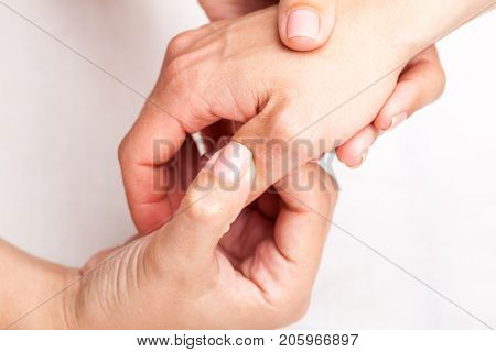 Young woman's thumb joint being manipulated by osteopathic manual therapist or physician