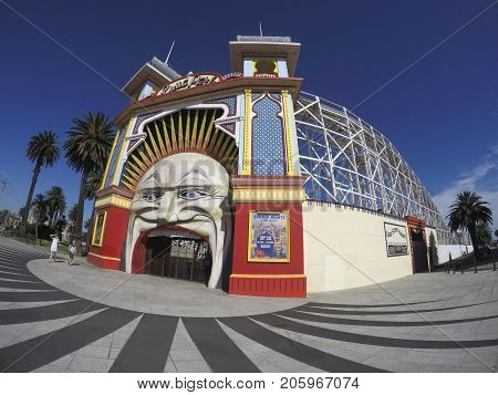 Melbourne, Australia: January 12, 2015: Main Gate of Luna Park. Melbourne's Luna Park is an historic amusement park located on the foreshore of Port Phillip Bay in St Kilda. Tourists walk by.