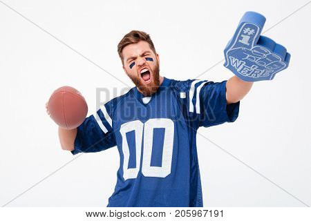 Happy agitated bearded man with painted face holding fan toys and looking camera isolated over white