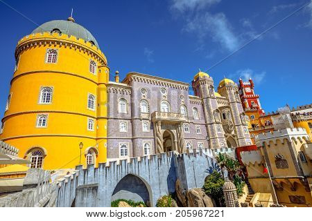 The colors and different architectural styles of National Palace of Pena, one of the seven wonders of Portugal and Unesco Heritage. Popular landmark of Sintra near Lisbon. Sunny day in the blue sky.