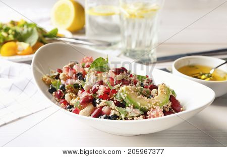 Superfood salad with avocado, beans and pomegranate seeds in white bowl on kitchen table