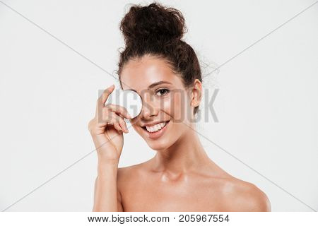 Close up beauty portrait of a happy young woman with soft healthy skin removing make up with cotton pad and looking at camera isolated over white background