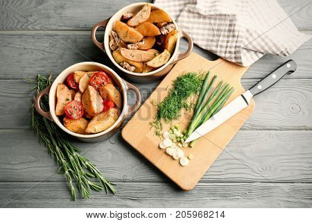 Casseroles with delicious baked potato wedges on wooden background