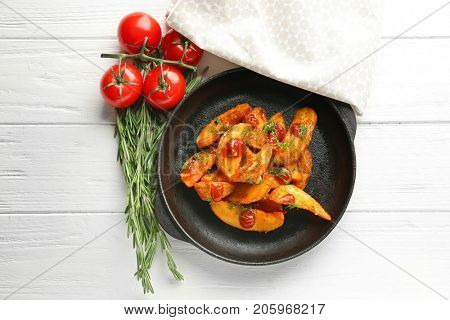 Frying pan with delicious baked potato wedges on wooden background