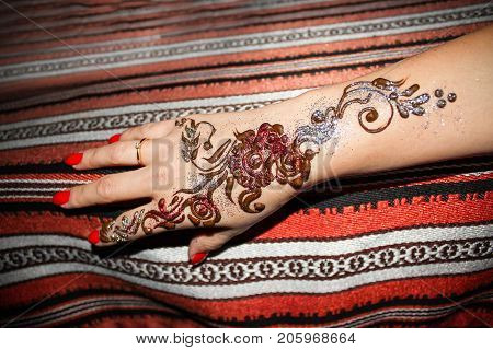 Woman hand with pattern of brown henna. Hand with mehndi. Traditional Arabic style background. Indian fashion. Selective focus.
