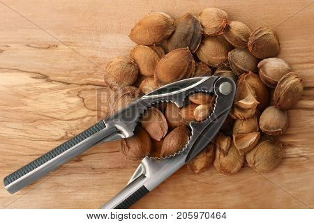 Nutcracker tool with apricot kernels on wooden background