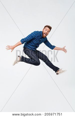 Full length portrait of a happy excited bearded man jumping and looking at camera isolated over white background