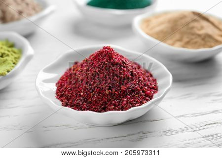 Maqui berry powder in white ceramic bowl on wooden background