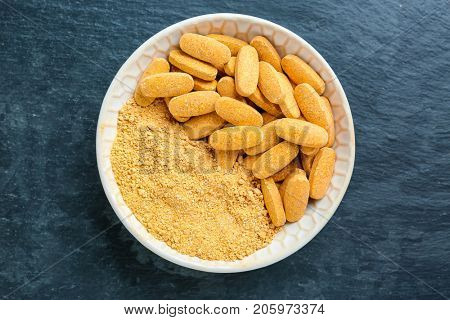 Camu powder and pills in white ceramic bowl on dark background