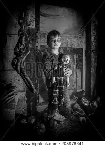 Photo of a creepy young boy holding an old clown doll in an old barn covered in spiderwebs and dust.