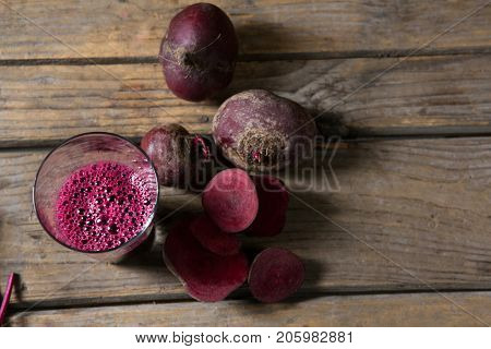 Overhead of beetroot and beetroot juice on wooden table