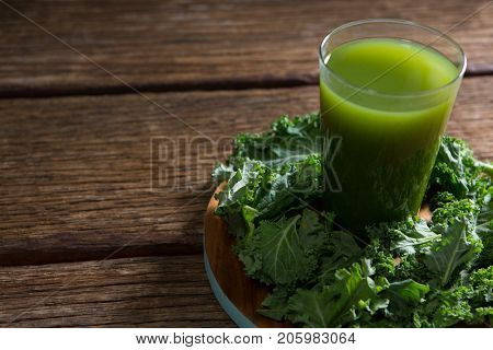 Close-up of mustard greens and juice on wooden board