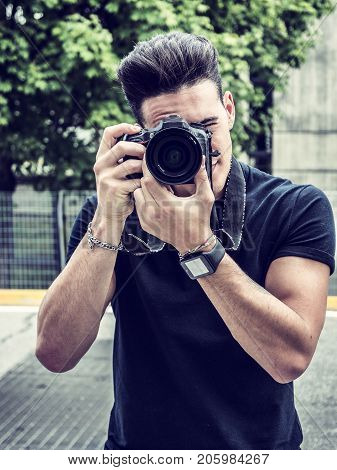 Handsome young male photographer taking photograph with professional photo camera hanging from his neck