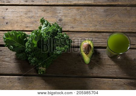 Overhead of mustard greens, avocado and juice on wooden table