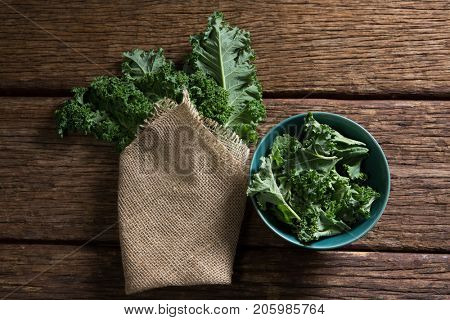 Overhead of mustard greens on wooden table