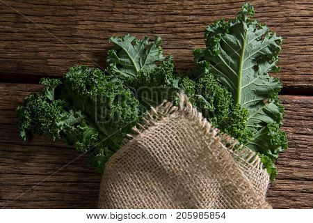 Close-up of wrapped mustard greens on wooden table