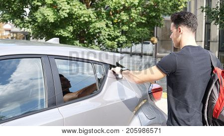 Young handsome man putting a backpack on the back seat, then getting on his car then fastening seat belt for his safety, just about to turn the engine on