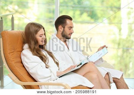 Young loving couple in bathrobes reading magazines in spa salon
