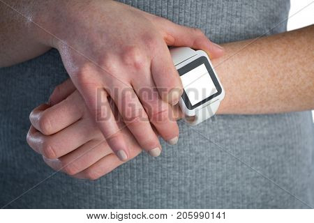 Businesswoman adjusting smart watch while standing against white background