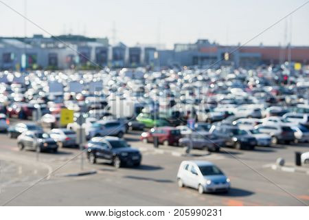 Abstract blurred view with bokeh light of full parking lots next mall complex, outdoor. Uncovered crowded parking modern shopping center, retail store, Top view, for background