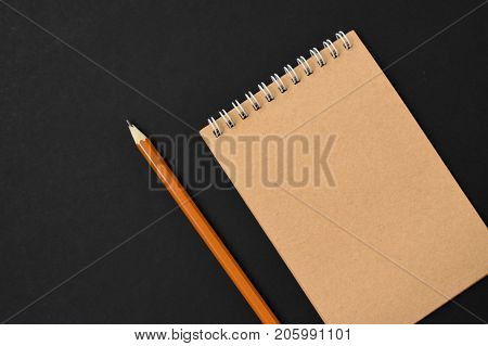 Top view of open spiral blank notebook with pencil on black paper background. Open vintage notebook. Empty notebook paper for text with  pencil . office concept top view.Copy space. Space for text.