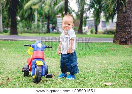 Cute little Asian 1 year old toddler baby boy child riding his tricycle in summer park kid playing toy and cycling in the garden outdoors on nature Child first experience concept