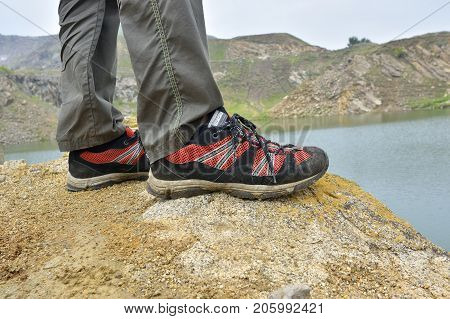 Walking shoes. All terrain shoes. Hiking shoes on hiker outdoors walking crossing river creek. Woman on hike trekking in nature. Closeup of female hiking shoes in action. Trekking shoes