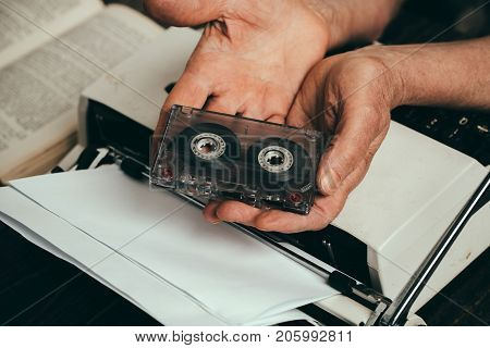 Retro music typewriter and old woman. Mature woman holds cassette for tape recorder in hands above antique typewriter with white clean paper for writer inspiration for hobbies art and creativity