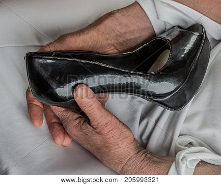 Old retro fashion for mature women. Old woman holds shoe woth high heels. Youth and old age concept fashion retro and memories. Women's shoes elderly bride with black shoes in old hands wrinkles