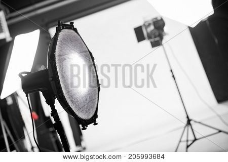 Photography studio with professional lighting equipment. Focus on a beauty dish with a grid.