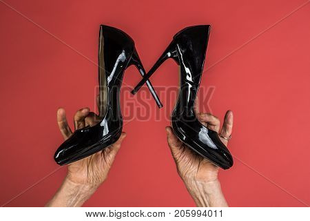 Glamor vintage shoes in hands of old woman last century black leather lacquer shoes in old hands with wrinkles. Fashion and fashionista grandmother. High heel for mature women. Evening style