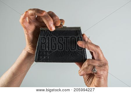Retro wallet old female hands hold vintage handbag for money coin purse of genuine leather. Antique decorations and accessories. Ring and purse of old woman elegant mature women's hands with jewels