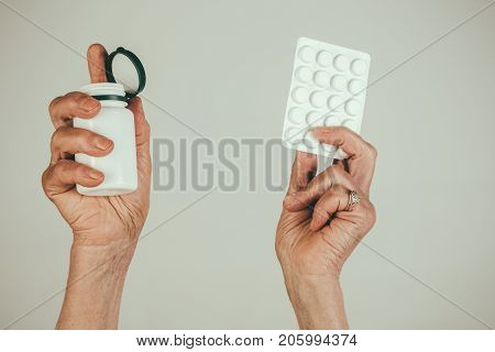 Pills medications hands. Old female hands hold pills in Blister Pack and pill bottle packaging for drugs: painkillers antibiotics vitamins. Medicine health care close up mature woman hold pill