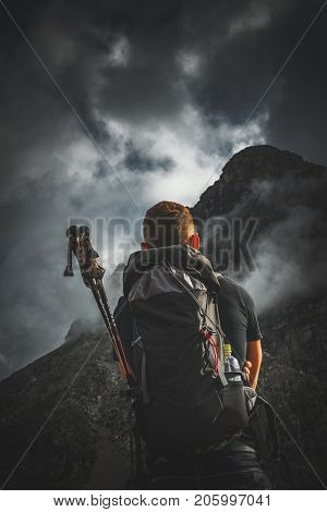 A mountain climber with backpack and climbing equipment looking towards a stormy, fog shrouded summit.
