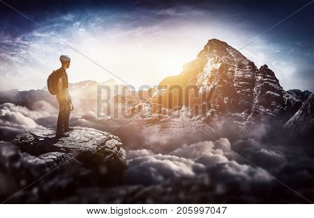 A mountain climber standing on a summit with a majestic sunrise view over towering snow capped mountains and cloud tops.
