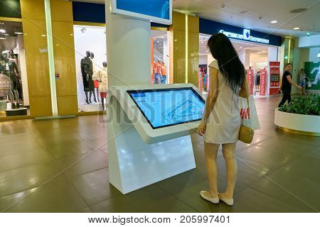 SAINT PETERSBURG, RUSSIA - CIRCA AUGUST, 2017: woman use information kiosk at Galeria shopping center. Galeria is major shopping and entertainment center is located in downtown of St. Petersburg