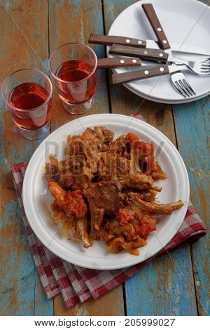 Roasted lamb chops with tomato and pepper on a rustic table