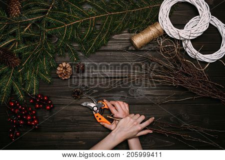 Florist Making Christmas Wreath With Branches