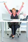 Excited modern business woman sitting at office desk and rejoicing her success poster