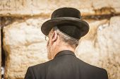 Religious Jewish man seen from the back, Orthodox Jew praying at the Western wall (Wailing wall), Jewish prayer. Orthodox Judaism, Jewish holidays stock image. poster