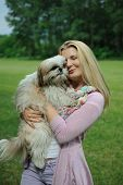Pretty casual woman with cute little shih tzu dog outdoors in a park poster
