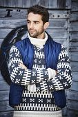 Handsome rugged guy in patterned knitwear and body warmer looking away poster