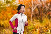 Active woman running and jogging. Middle aged Asian mature female jogger outdoor living healthy lifestyle in beautiful autumn city park in colorful fall foliage. Asian Chinese lady in her fifties. poster