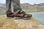 Walking shoes. All terrain shoes. Hiking shoes on hiker outdoors walking crossing river creek. Woman on hike trekking in nature. Closeup of female hiking shoes in action. Trekking shoes poster