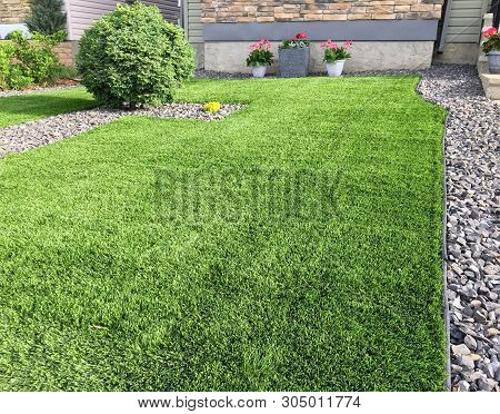 A Beautiful Artificial Lawn In The Front Yard With Nice Flowers And Shrubs Surrounding It